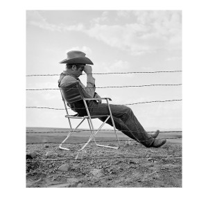 James Dean seated behind a Fence